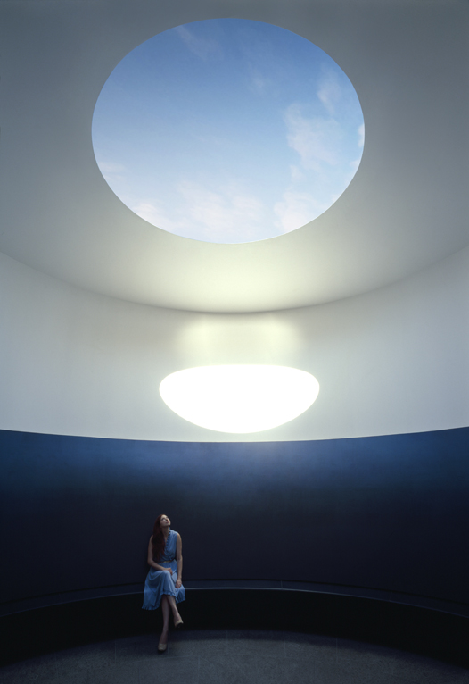 Photo of a young woman seated in the skyspace.