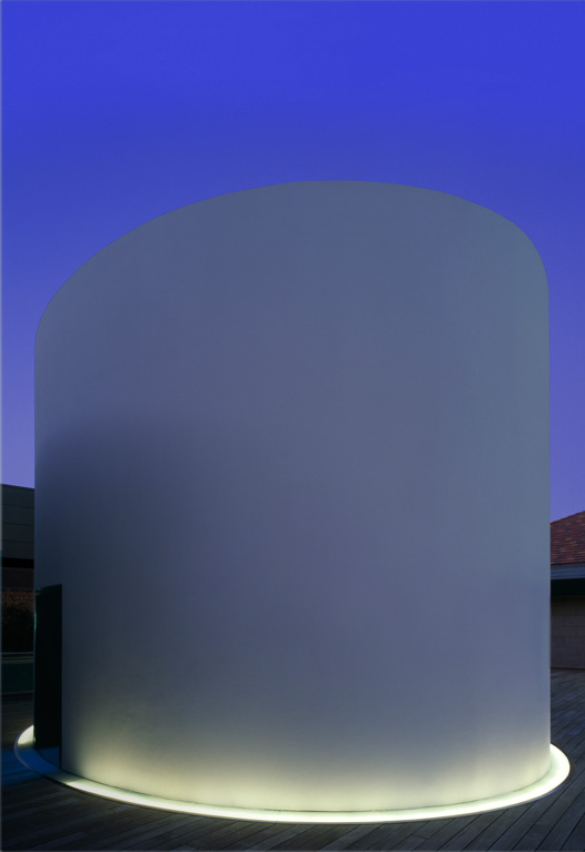 Photo of the exterior of the structure illuminated at dusk.